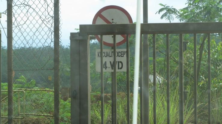 Pintu gerbang areal tambang, disertai rambu peringatan dilarang masuk kecuali mobil 4-WD